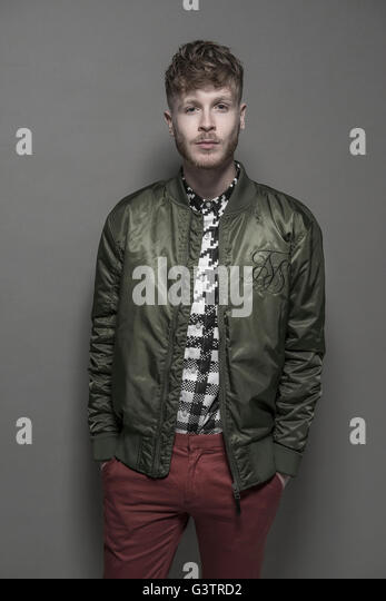 Studio portrait of a bearded young man wearing a green bomber jacket. - Stock-Bilder