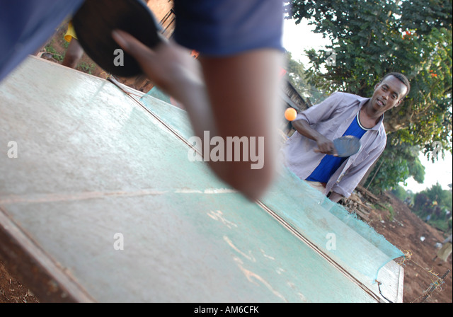 Ethiopian coffee farmers relax by playing table tennis in Choche village after a day picking coffee, Ethiopia - Stock Image