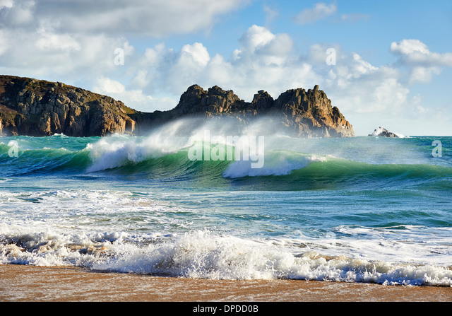 A curling wave breaking at the beautiful Porthcurno beach - Stock Image