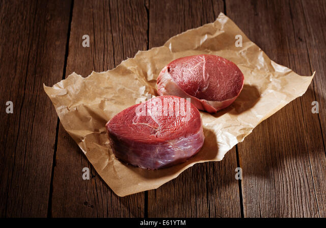 Raw beef steak on wooden table. - Stock Image