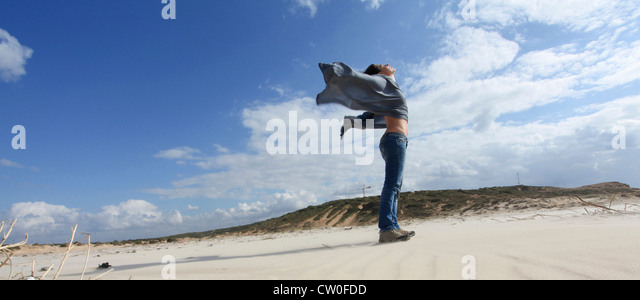 Woman standing on windy beach - Stock Image