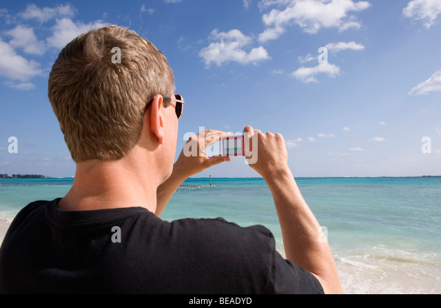 Rear view of a man using a digital camera, Cable Beach, Nassau, Bahamas, Caribbean - Stock-Bilder