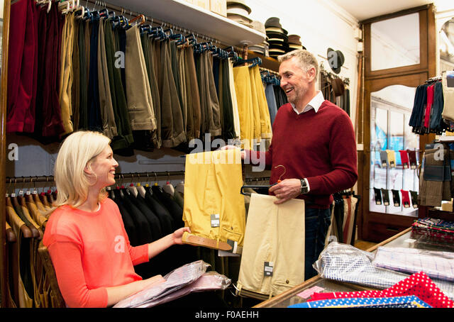 Couple browsing trousers in tailors shop - Stock Image