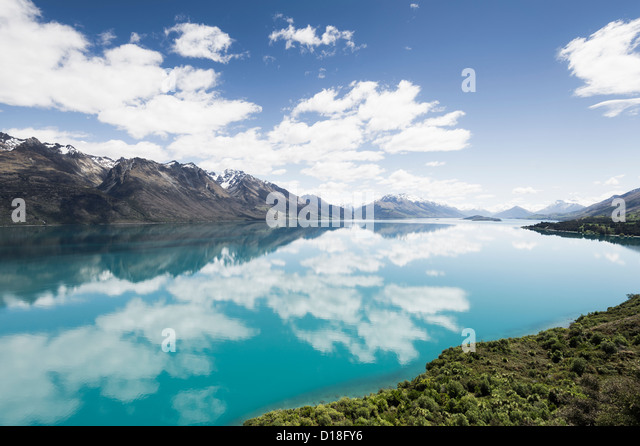 Clouds and sky reflected in still lake - Stock Image