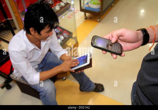 Thailand Bangkok Ratchathewi Pratunam Market marketplace Asian man smartphone tablet iPad using texting checking - Stock Image