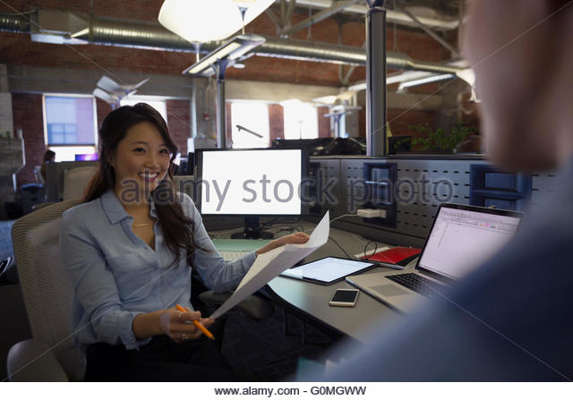 Smiling businesswoman with paperwork at desk - Stock Image