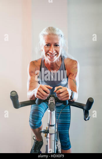 Caucasian woman riding stationary bicycle - Stock Image