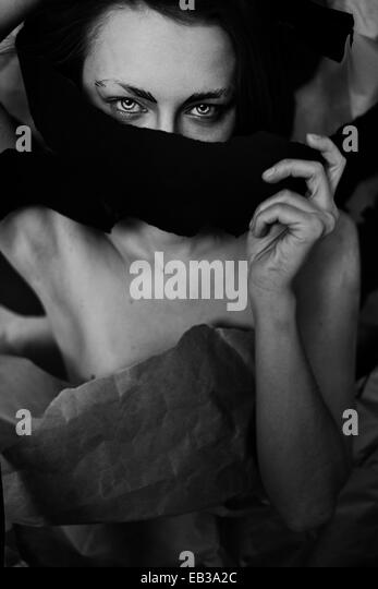Portrait of woman wrapped in scarf and paper - Stock Image