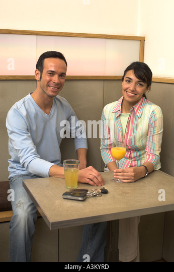 portrait of young man and woman sitting at a table in cafe - Stock Image