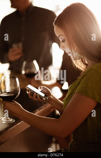 Businesswoman looking at cellphone in a wine bar - Stock Image