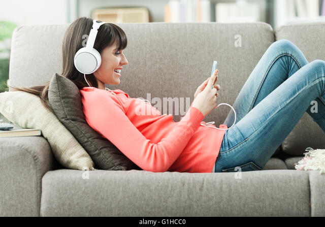 Attractive young woman on the sofa at home, she is playing music with her smarphone and wearing headphones, leisure - Stock-Bilder