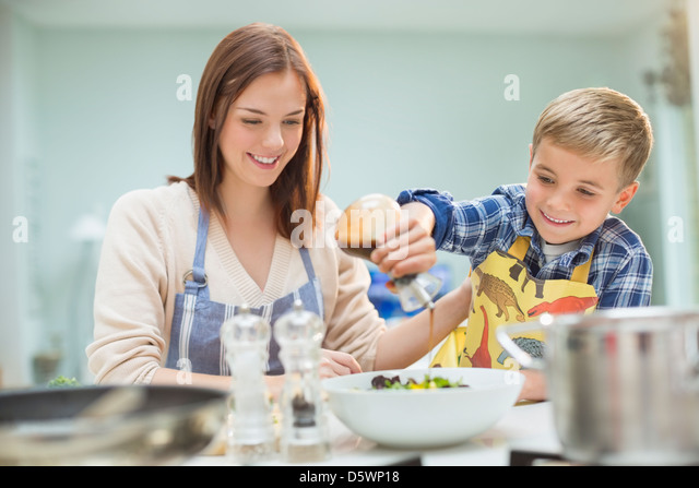 Mother and son making salad in kitchen - Stock Image