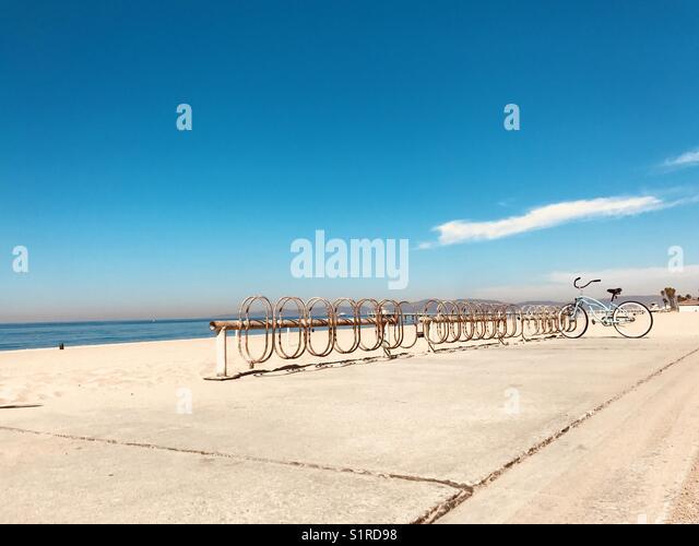 A blue bike parked in a bike rack at the beach. Manhattan Beach, California USA. - Stock Image
