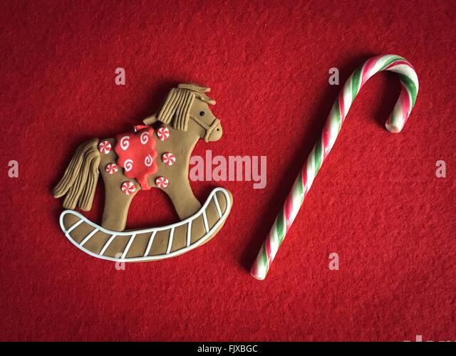 Close-Up Of Animal Shaped Gingerbread Cookie And Candy Cane On Red Fabric - Stock-Bilder