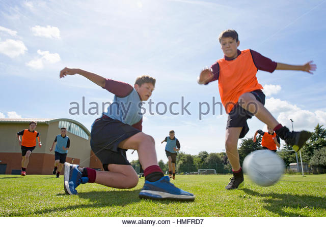 Middle schoolboys playing soccer on sunny field in physical education - Stock-Bilder