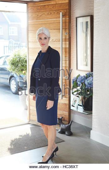 Mature businesswoman standing at open door. - Stock Image