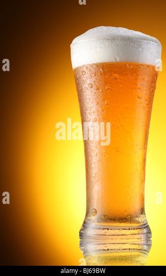 glass of beer on a brown background - Stock Image