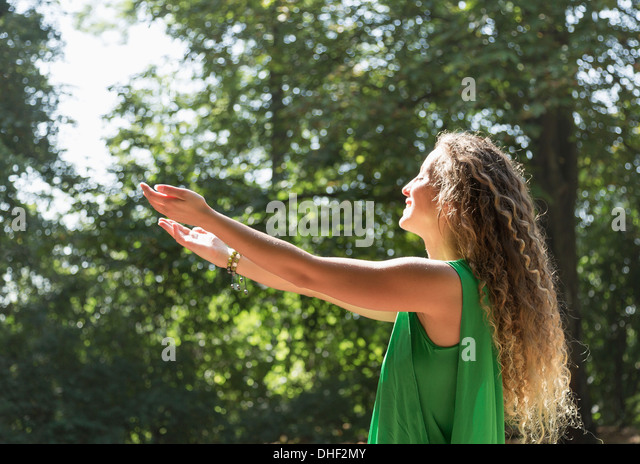 Teenage girl wearing green top with arms out, Prague, Czech Republic - Stock-Bilder
