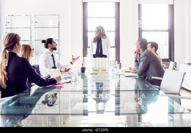 Businesswoman explaining to colleagues during board meeting - Stock-Bilder
