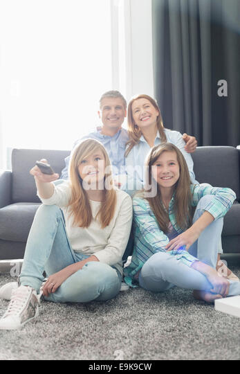 Happy family of four watching TV together at home - Stock Image