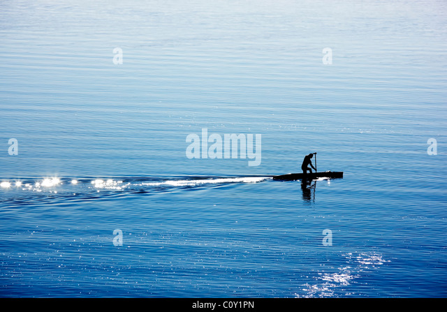 silhouette of canoe rower on lake - Stock Image
