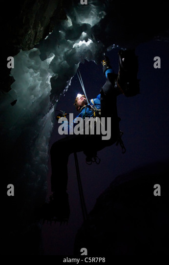 Ice Climbing at night on the edge of a cave. - Stock-Bilder