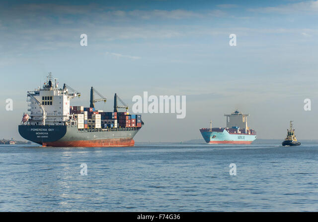 The container ships, Pomerenia Sky and Maersk Lota steaming past each other as they sail on the River Thames. - Stock Image