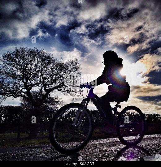 Young girl cycling in front of the sun - Stock Image