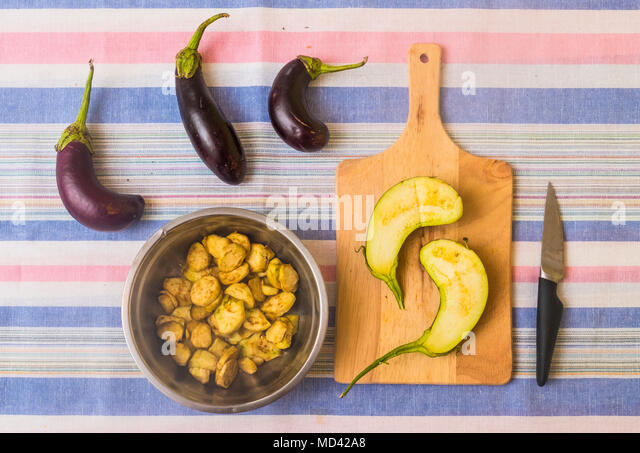 Aubergines, with sliced aubergine on chopping board and pan with prepared food - Stock Image