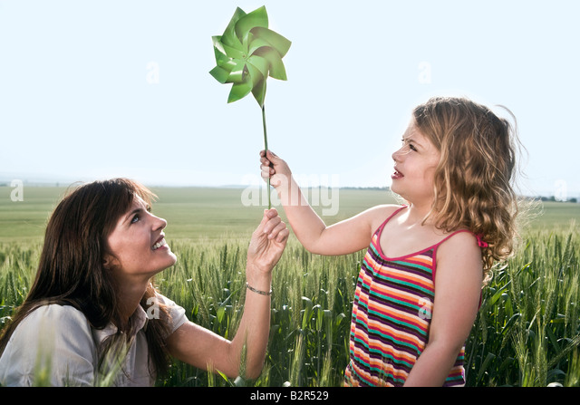 Woman and child holding toy windmill - Stock Image
