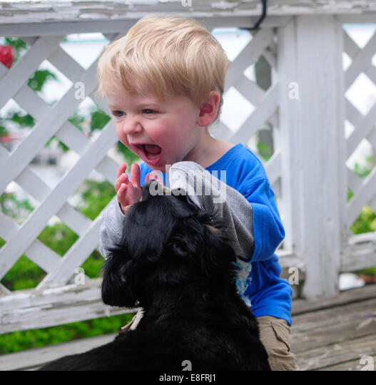 Portrait of a boy playing with his puppy dog - Stock Image
