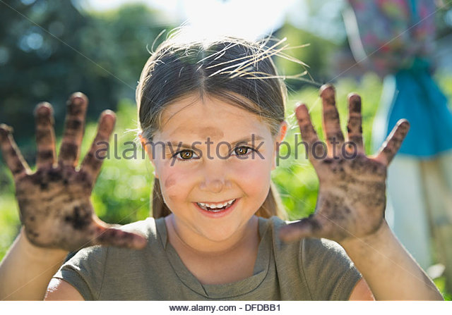 Portrait of little girl showing hands full of dirt - Stock Image