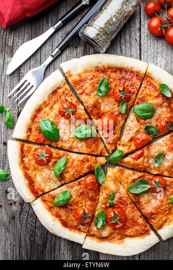 Italian pizza Margherita on a wooden table - Stock Image
