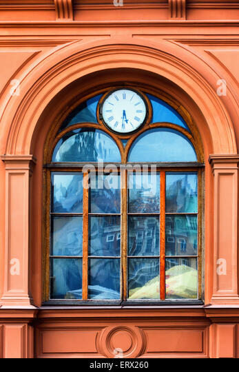 Window Clock Riga Stock Exchange and the reflection in the glass of the old city of Riga - Stock Image