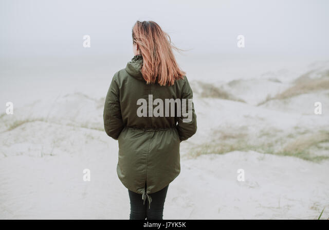 Woman standing on empty beach in winter time - Stock Image