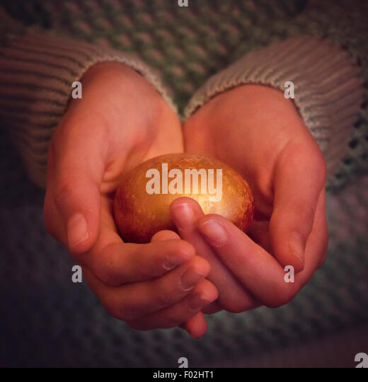 A girl holding golden nest egg in her hands - Stock Image
