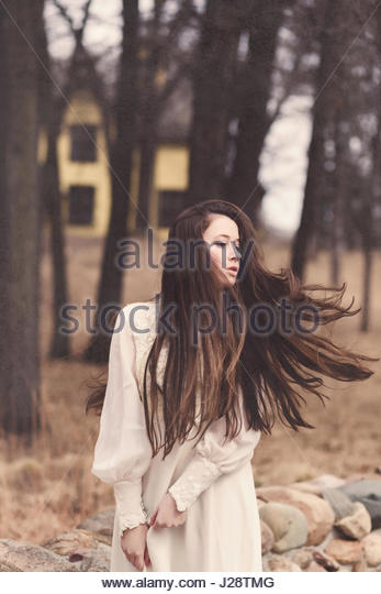 Young brunette woman with very long hair standing in front of a Victorian house - Stock Image