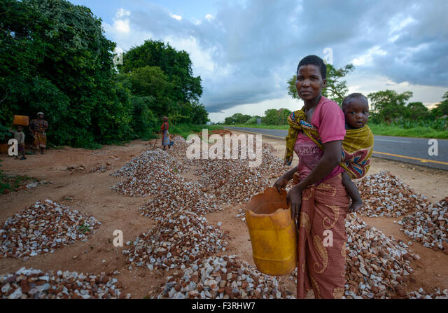 Woman with baby collects stones, Mozambique, Africa - Stock Image