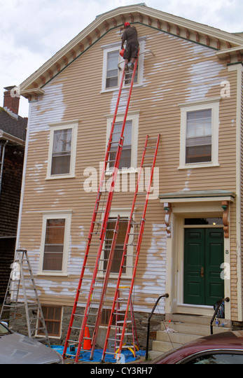 Rhode Island Newport Barney Street house painter ladder tall high Black man dangerous job siding - Stock Image