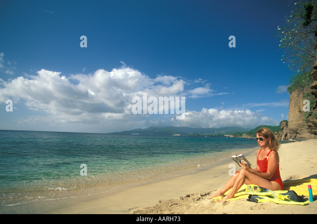 Grenada beach single woman on isolated  beach reading book vacation paradise - Stock Image