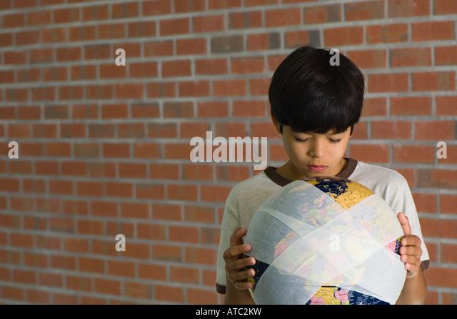 Boy holding bandaged globe, front view - Stock Image