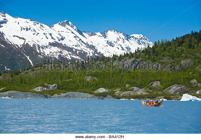 Native Alaskans canoeing in traditiional voyager canoe at Spencer Glacier, Alaska - Stock Image