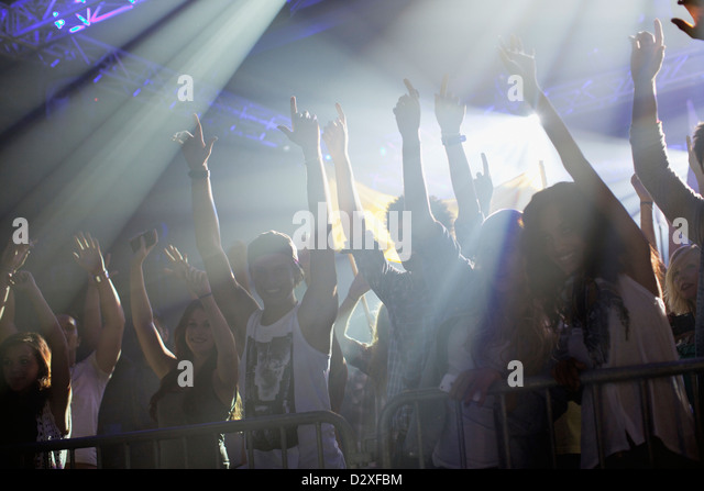 Crowd with arms raised behind railing at concert - Stock Image