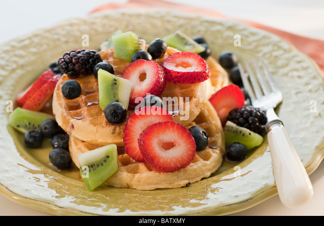 Waffles with berries and kiwi on plate - Stock Image