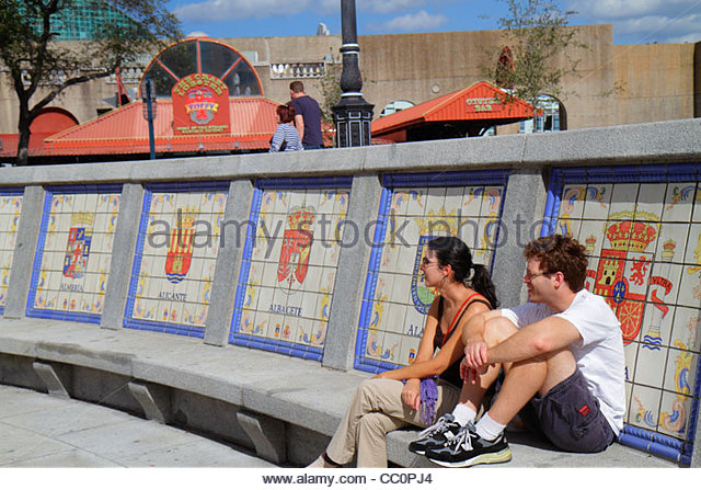 Louisiana New Orleans Spanish Plaza public park square bench tiles seals coat of arms man woman couple resting relaxing - Stock Image