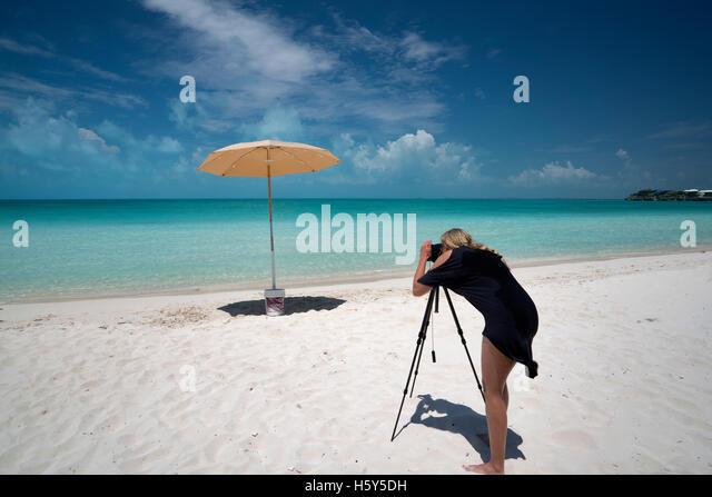 Photographer shooting umbrella Sappodilla Bay. P{rovidenciales, Turks and caicos - Stock Image