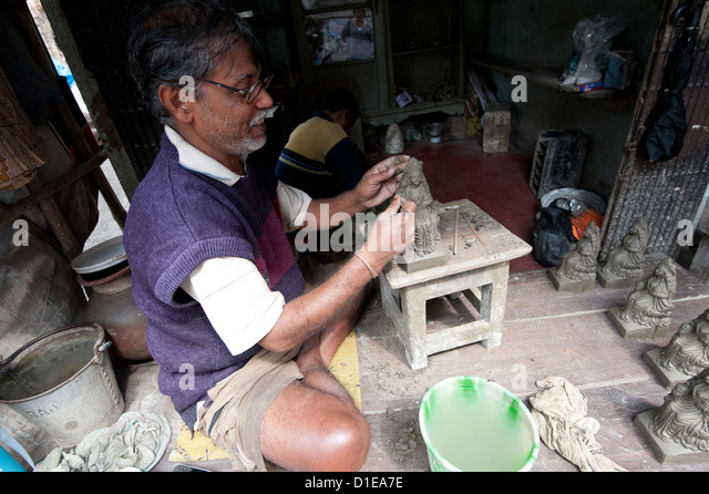 Master sculptor making models from clay from the River Hugli, Kumartuli district, Kolkata, West Bengal, India - Stock Image