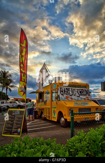 A woman buying a meal from a shrimp truck in Waikiki - Stock Image