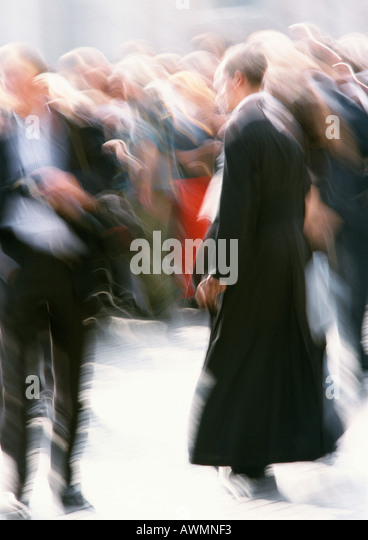 Priest walking in crowd outside, blurred - Stock-Bilder