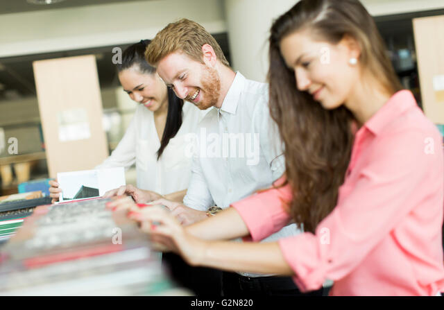 People standing by the bookshelves in the library - Stock Image